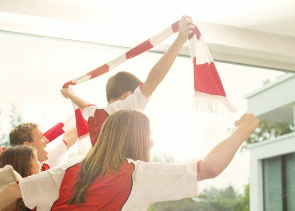 Family in red and white sports jerseys cheering in living room