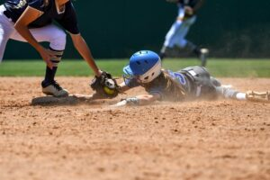 Young high school softball players in action, making amazing plays, during a game.