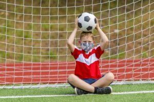 School kid with mask and soccer ball in a physical education lesson.