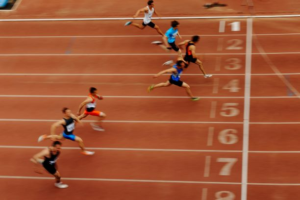 Seven sprinters running across the finish line of a red track.