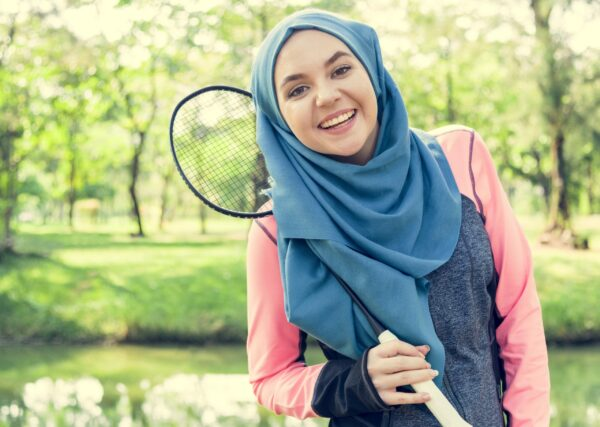 Woman in a park, holding a badminton racquet and smiling at the camera