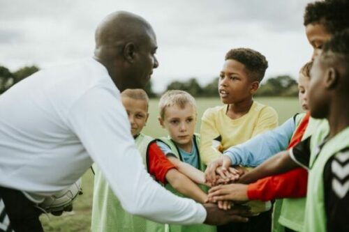 Coach in a huddle with a group of kids preparing for a game.