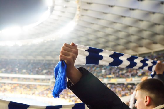 Sports fan in a stadium holding up a blue-and-white scarf to support his favourite team.