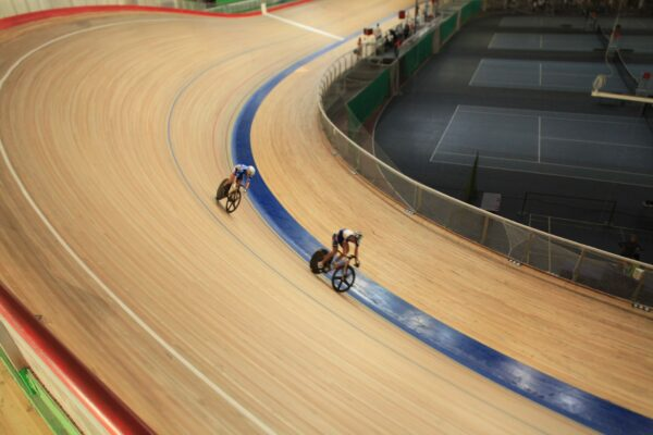 Two cyclists biking on an indoor wooden cycling track.