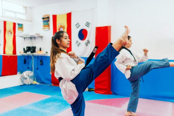 Two girls practicing high kicks in a karate gym with flags in the background.