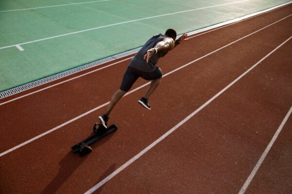 Person sprinting off the block on a track.