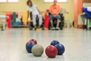 Closeup of boccia balls. Male and female players blurred in the background.