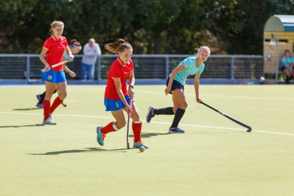 A girl in a red shirt playing field hockey on a sunny day. A player in a blue shirt is playing on defence.
