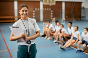 Portrait of happy physical education teacher during class at school gym.