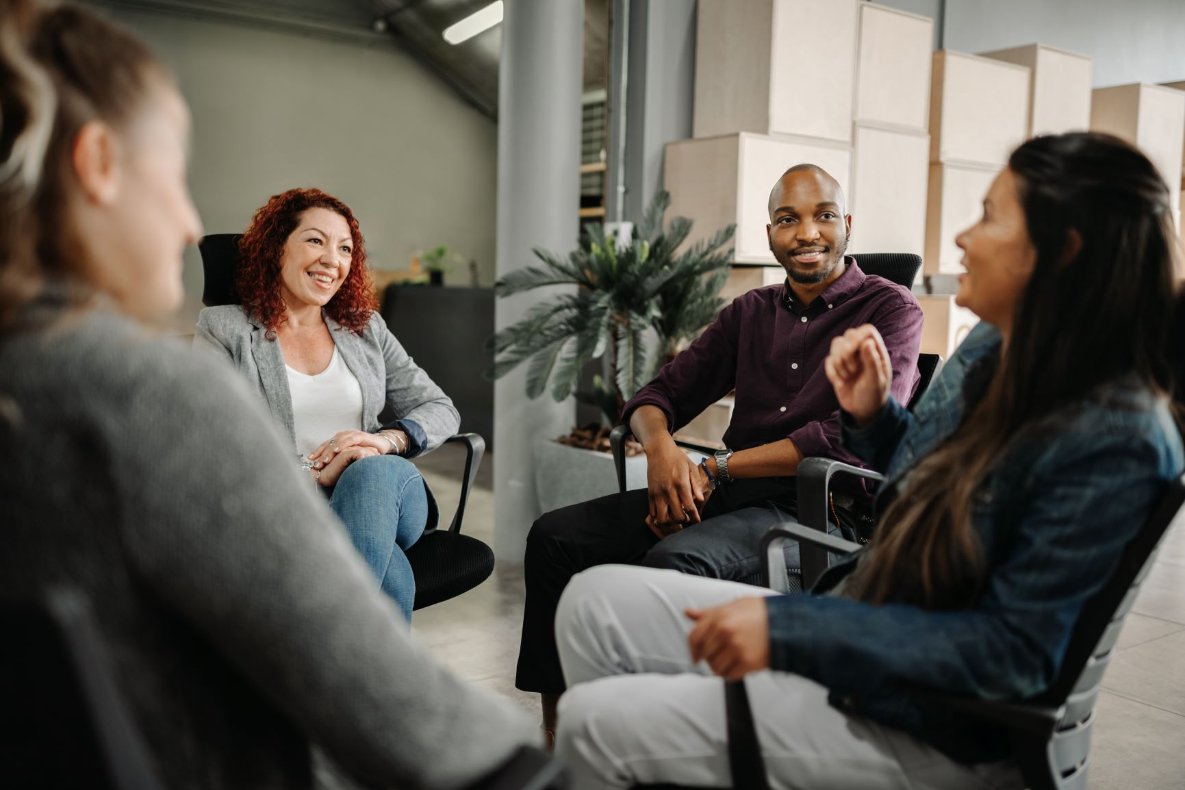 Group of four diverse colleagues sitting in a circle of chairs having a discussion.