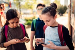 Two school-aged girls on smartphones while walking and wearing backpacks.