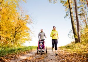 A dad pushing a stroller next to a mom who are both running outdoors in the Fall.