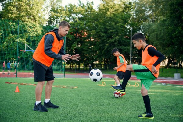 Soccer coach wearing an orange jersey throwing a ball towards a younger player who is kicking the ball back.