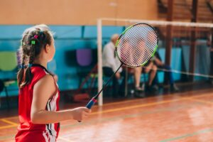 Rear view of a young girl playing badminton on a indoor court.