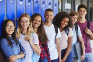 Group of diverse high school students standing in front of a row of lockers.
