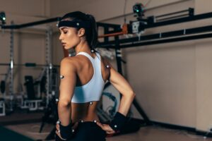 Female athlete standing looking over her shoulder while wearing motion capture equipment.