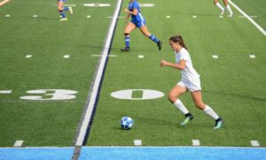 Teen female soccer player in Left wing position carrying the ball up the field