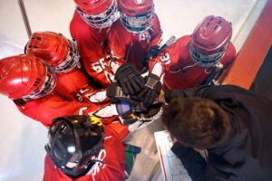 Youth hockey team putting hands together with coach in a huddle, showing teamwork