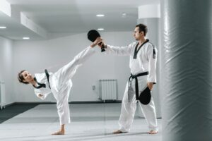 Young women with a disability practicing taekwondo with an instructor.