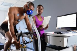 Man performing an exercise test on a stationary bike and wearing medical equipment.
