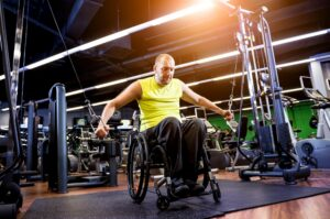 Man using a wheelchair working out in a gym.