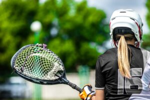Rear view of a young female lacrosse player wearing a helmet and holding equipment.