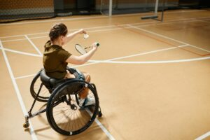High angle portrait of young woman in wheelchair playing badminton during sports practice at indoor court.