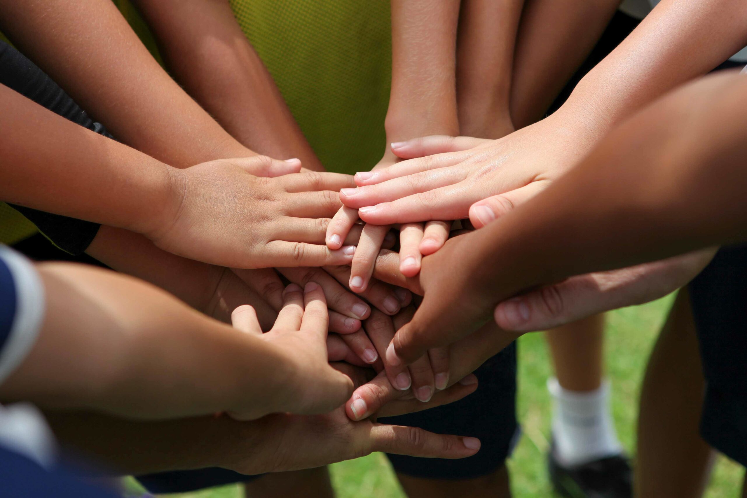 group of young people's hands in the centre of group ready to cheer
