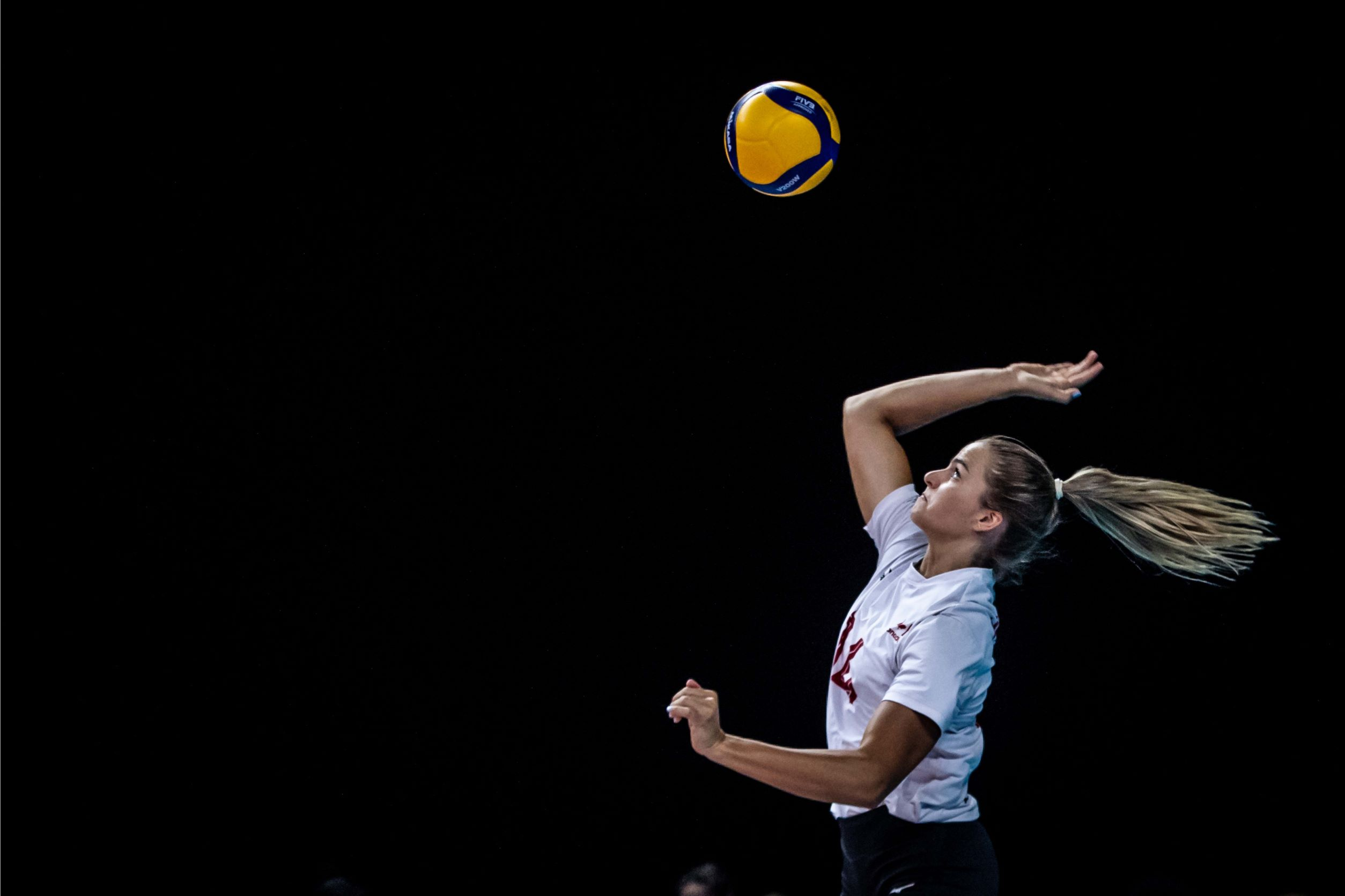 Side view of a female Volleyball Canada athlete jumping into the air to serve the ball, action shot against a black background.