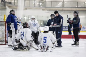 Youth hockey goalies being taught by a coach