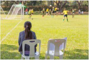 Une fille assise aux abords du terrain qui regarde les autres jouer au soccer
